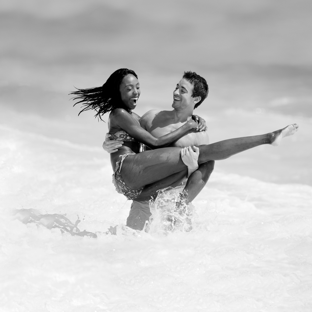 smiling man playfully carrying elated woman in his arms in the ocean