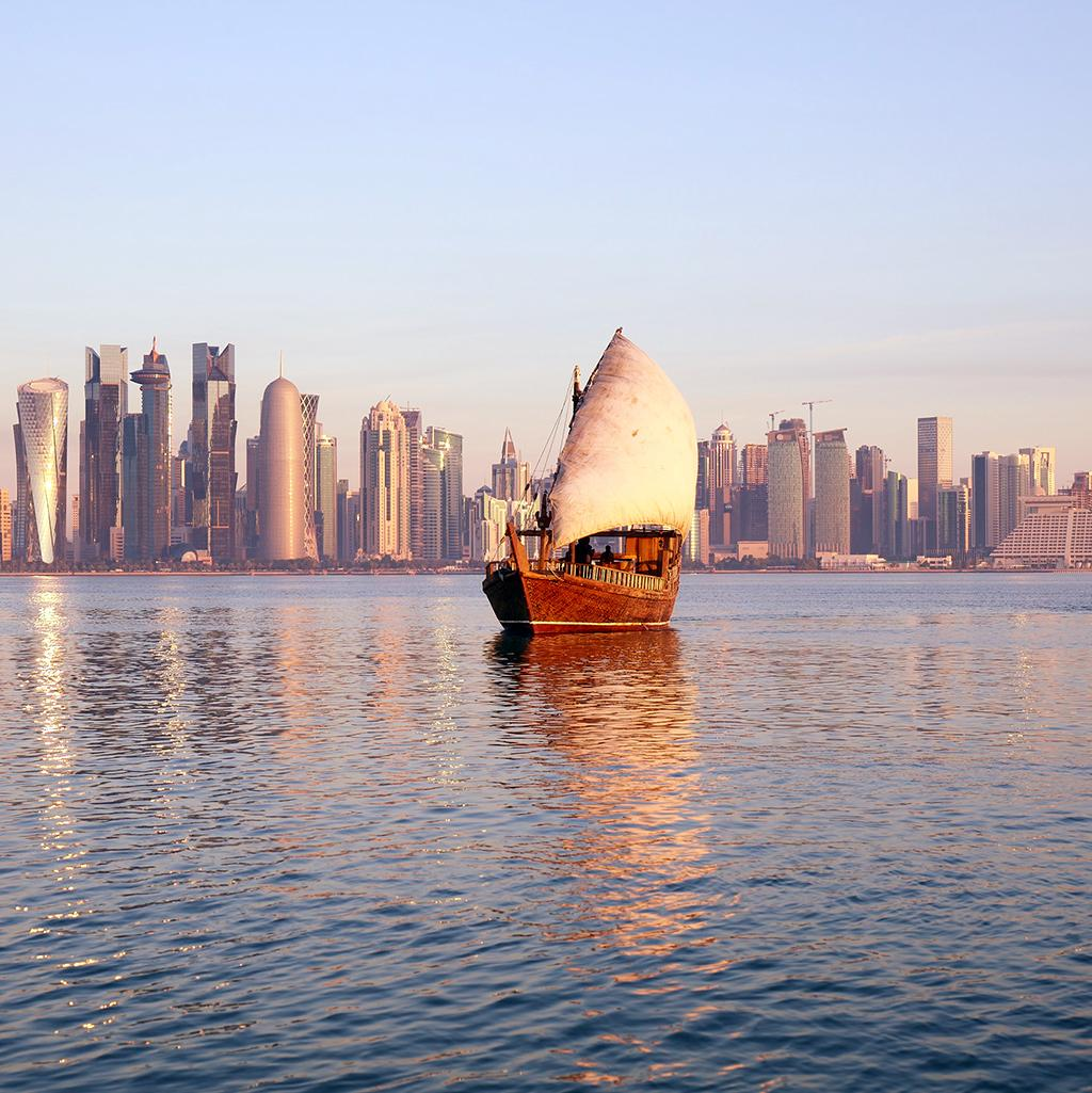 ship floating in the waters overlooking the skyline in Qatar