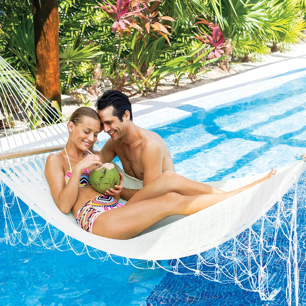 couple in hammock over a pool at an Excellence resort