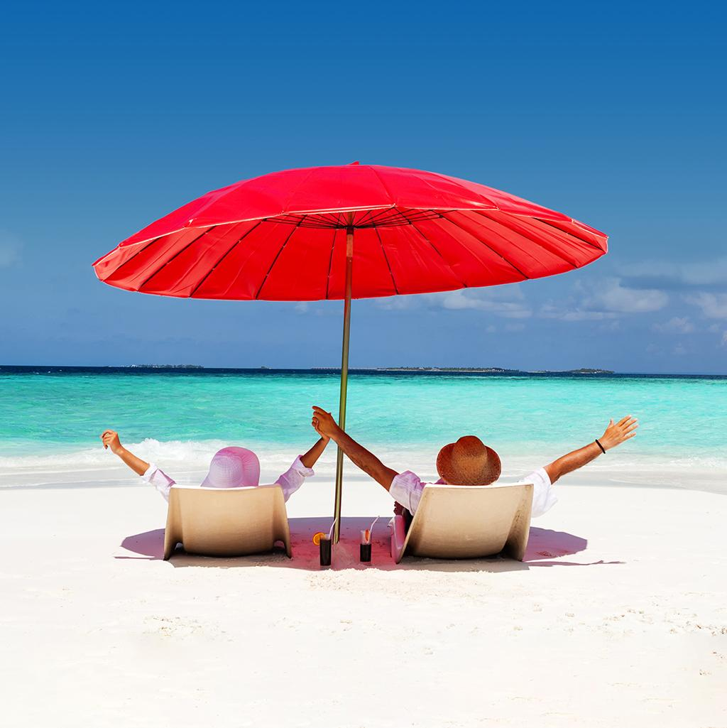 couple seated beneath a red beach umbrella on the beach overlooking the ocean