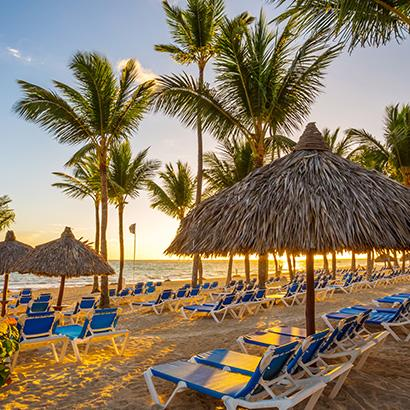 Beach chairs under thatched umbrellas in Punta Cana, Dominican Republic