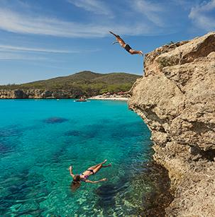 man jumping off a cliff into the blue waters of Curacao