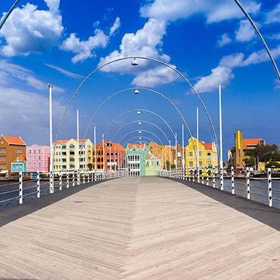 brightly colored buildings await visitors at the end of a boardwalk in Curacao