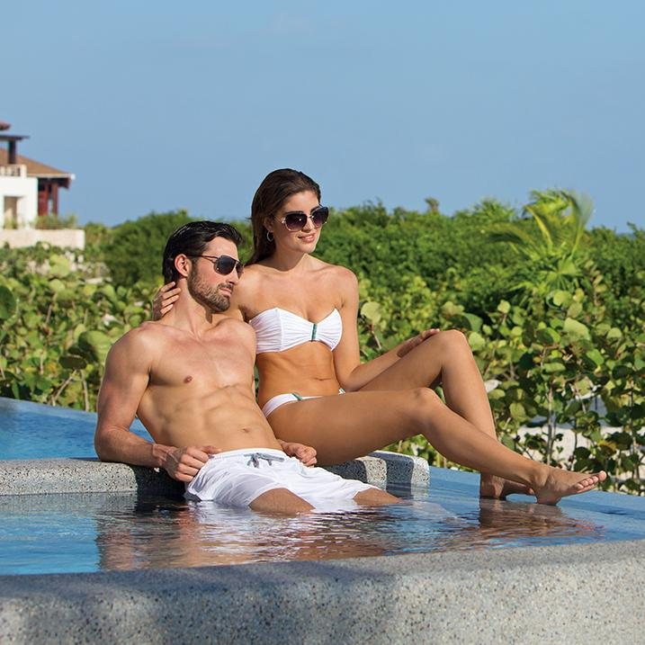 couple seated poolside at a Secrets resort