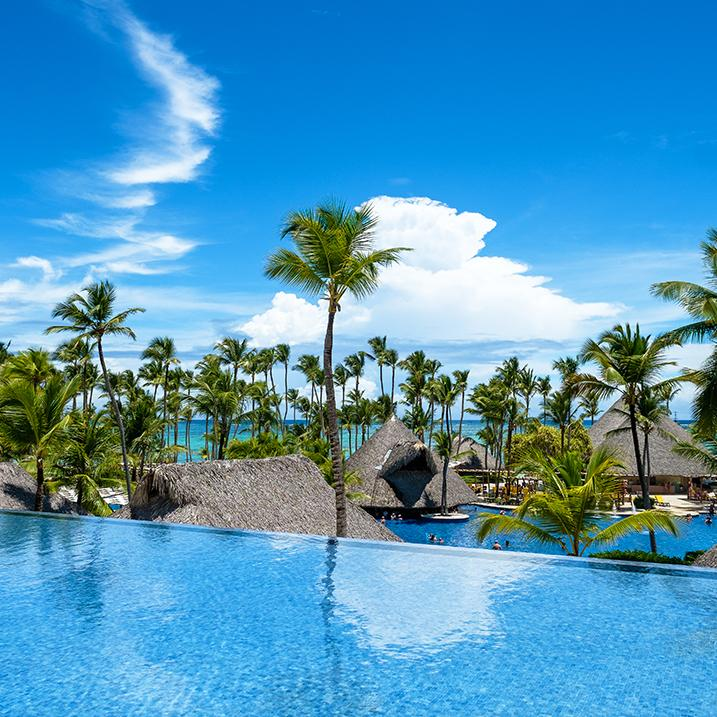 palm trees peek over the infinity pool at a Barcelo Maya resort