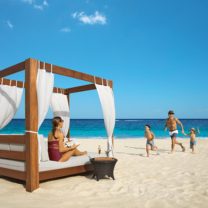 father running with 2 children to meet their waiting mother seated in a cabana on the beach at a Dreams Resort