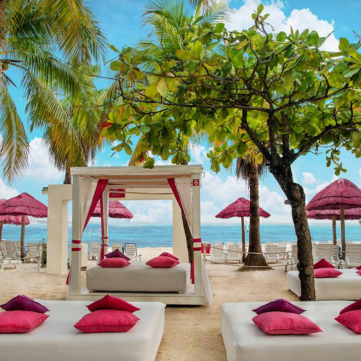 brightly colored red pillows and cabana tops adorn the beach at Grand Sens Cancun