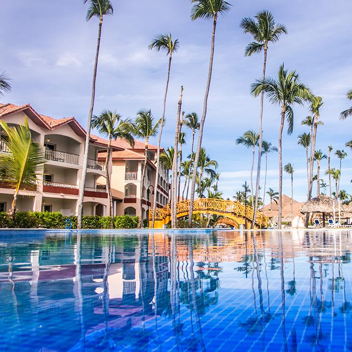 palm trees line the pool of a Majestic Resort