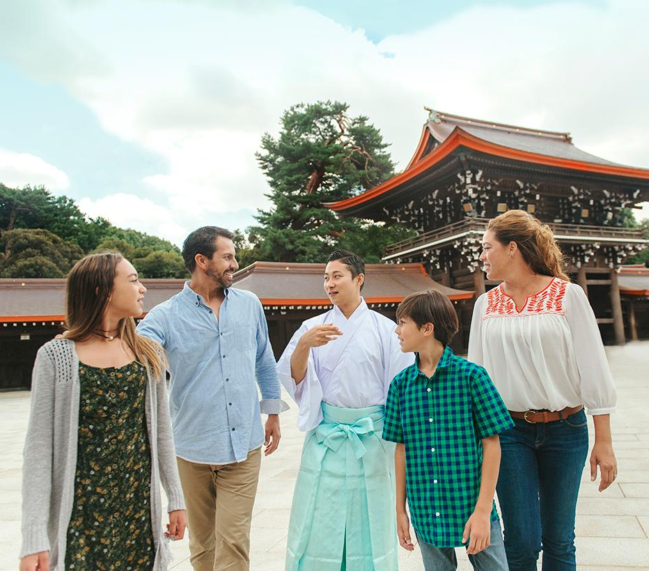 a family of four are guided from a Japanese temple by their tour guide
