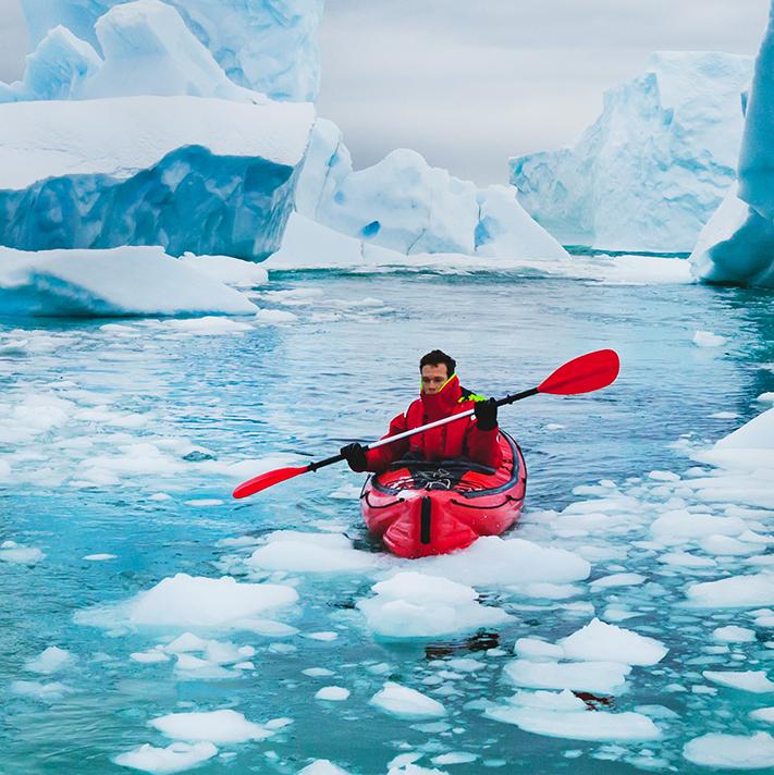 Man glacier kayaking in a red ice kayak