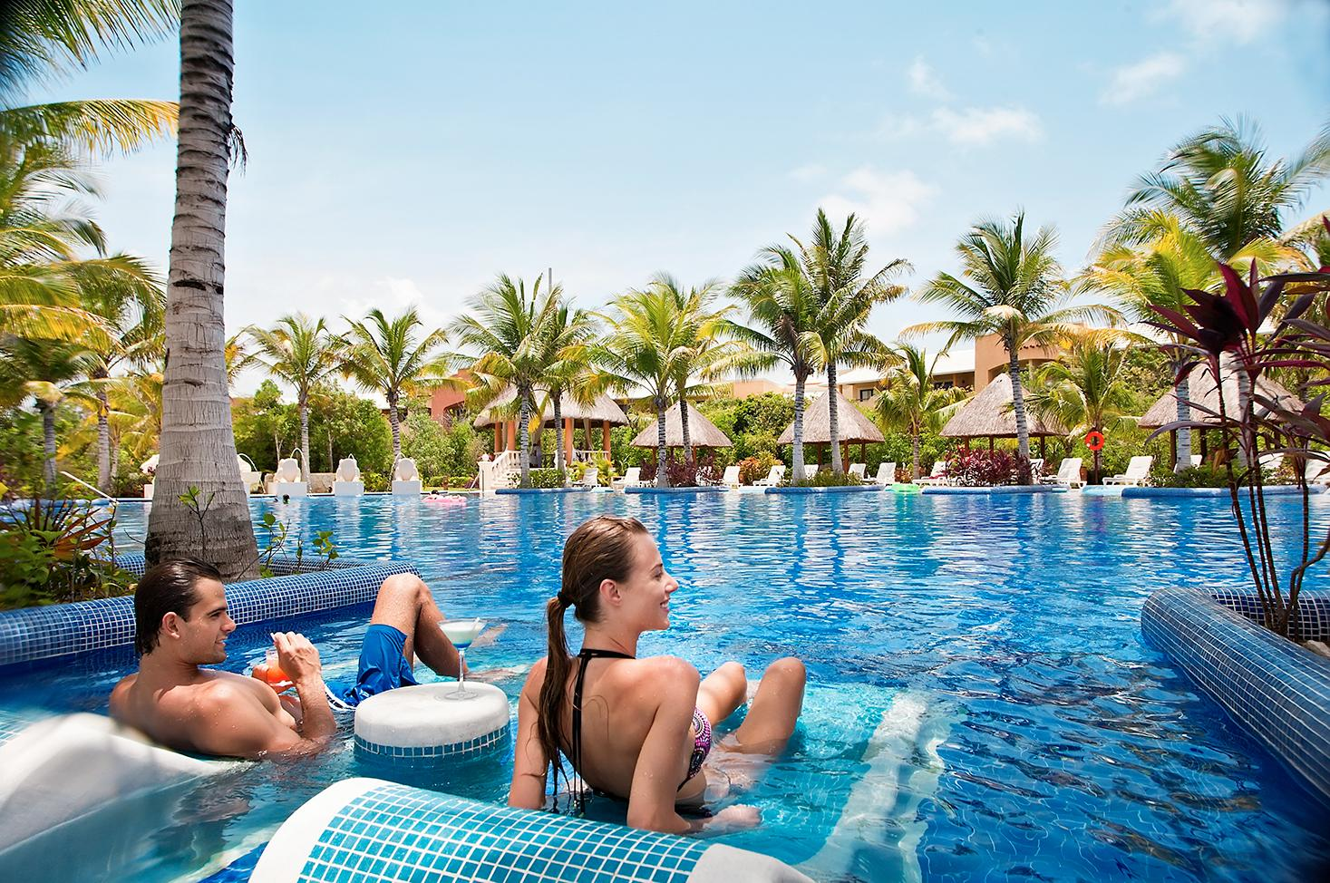 Couple relaxing in the pool at Barcelo Hotels & Resorts