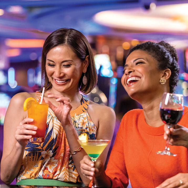 Two friends enjoy drinks on a Celebrity cruise