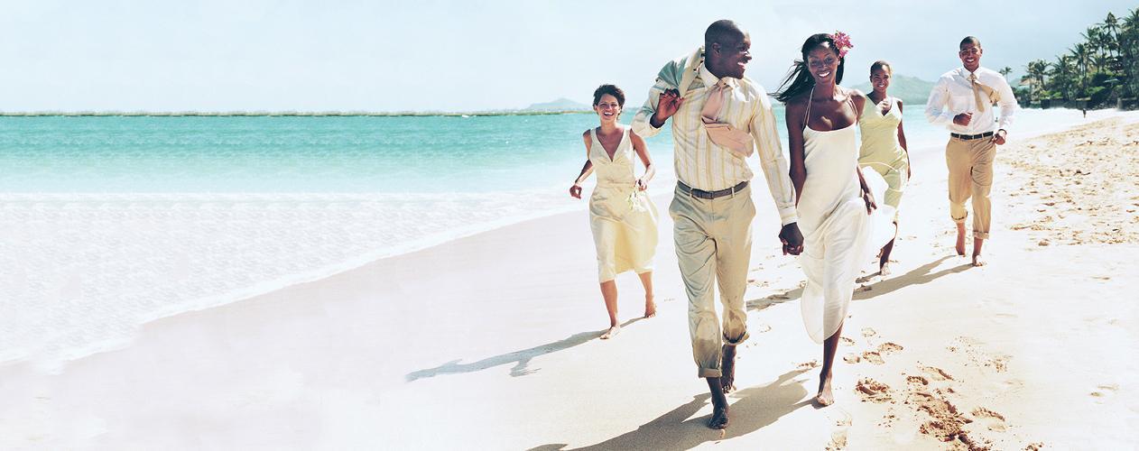 Destination wedding party running along beach