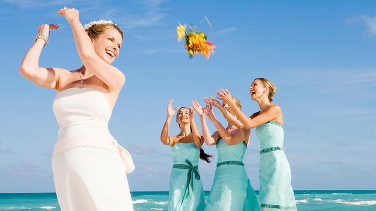 Bride bouquet toss to her bridal party at a beach destination wedding