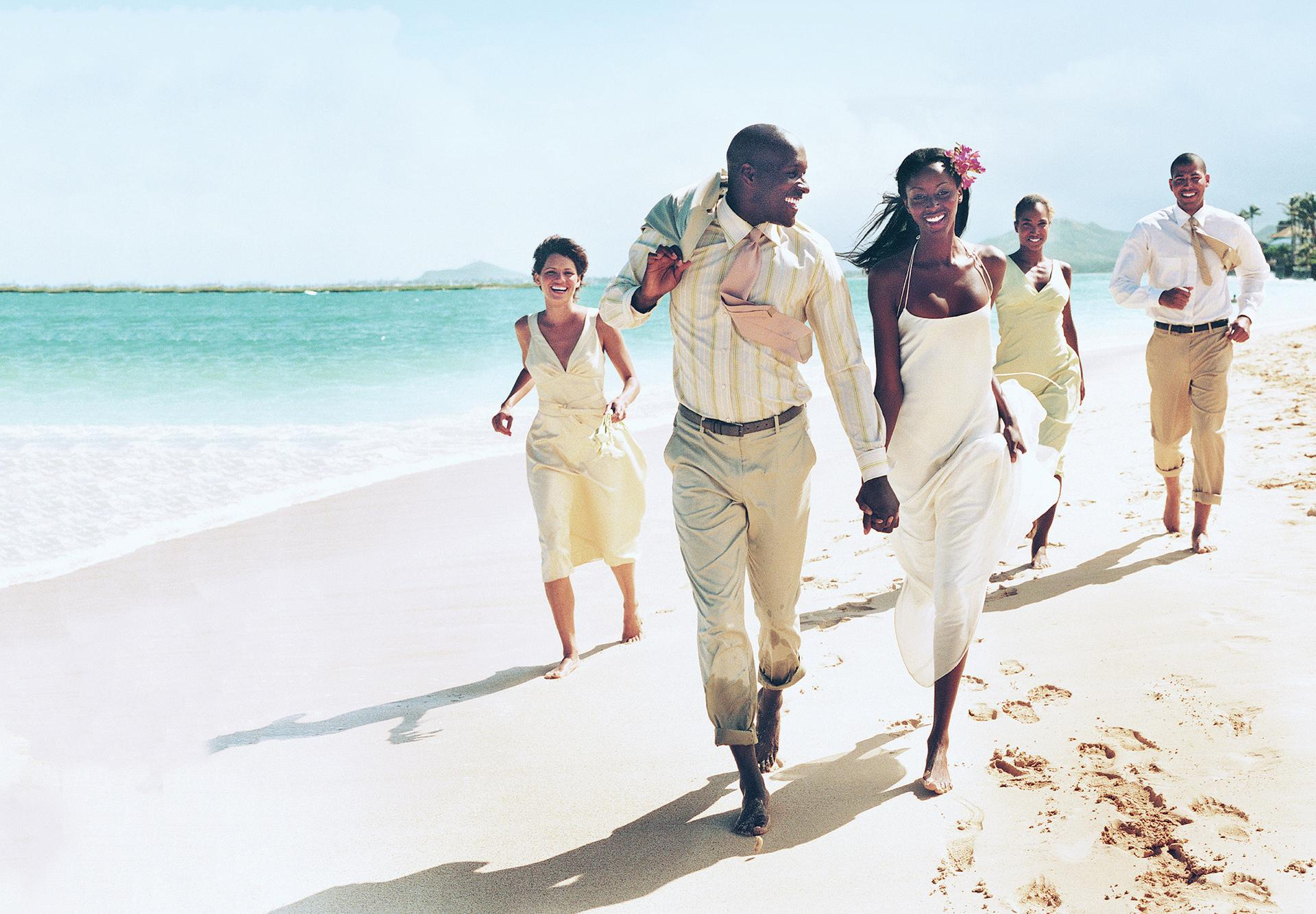 Destination wedding party running along the beach