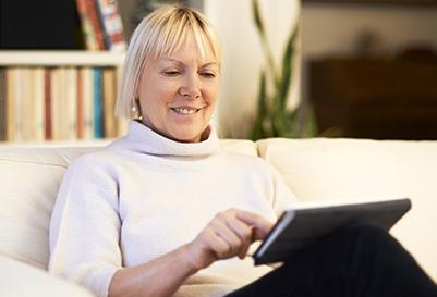 A woman reading on her tablet