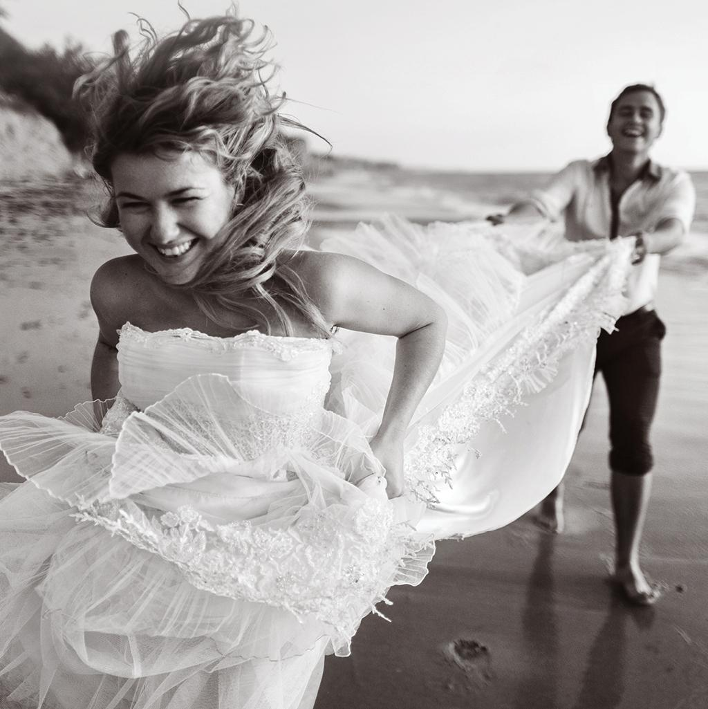 newly married couple frolicking along beach in wedding attire