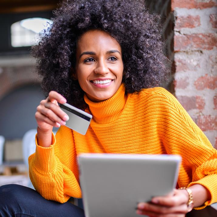 Woman holding a credit card in one hand and a tablet in another