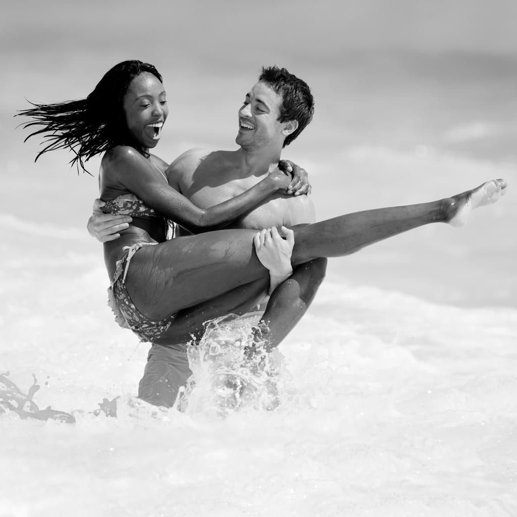 couple having fun in the ocean on their honeymoon