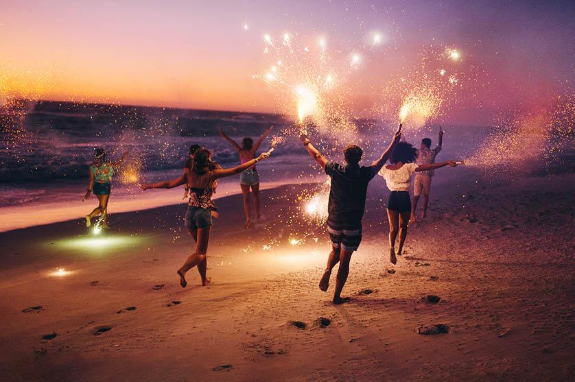 young group of 6 running along the beach at dusk with sparklers in their hands