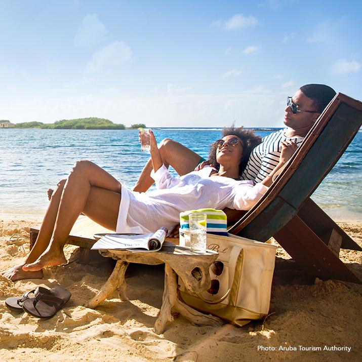 couple lounging on the beach in Aruba