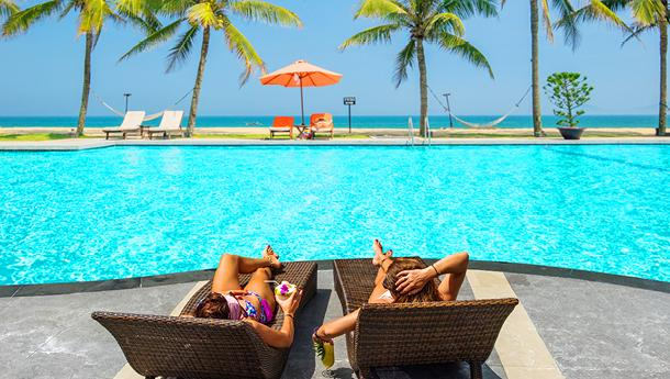 young man and woman soaking up the sun on lounge chairs at a resort pool