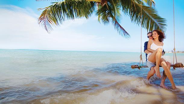 A happy couple on a beach swing