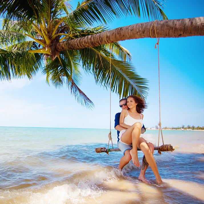 A couple relaxes on an overwater swing