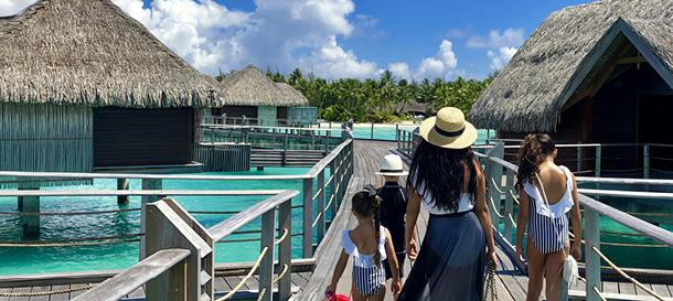 A family walks among overwater bungalows