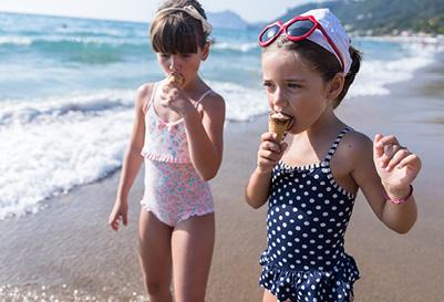 Kids enjoying ice cream in their bathing suits on the beach