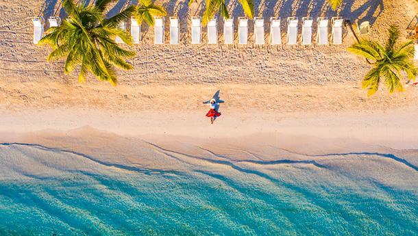 A woman enjoys the oceanfront in a Caribbean destination