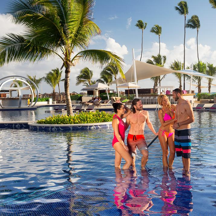 Two couples enjoy the pool on vacation at a Blue Diamond Resort