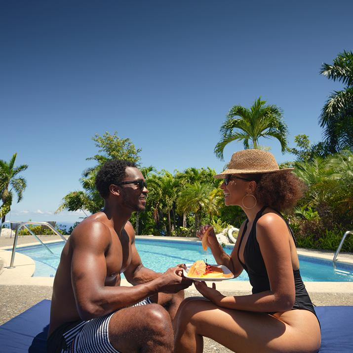 A couple enjoys a poolside snack in Jamaica