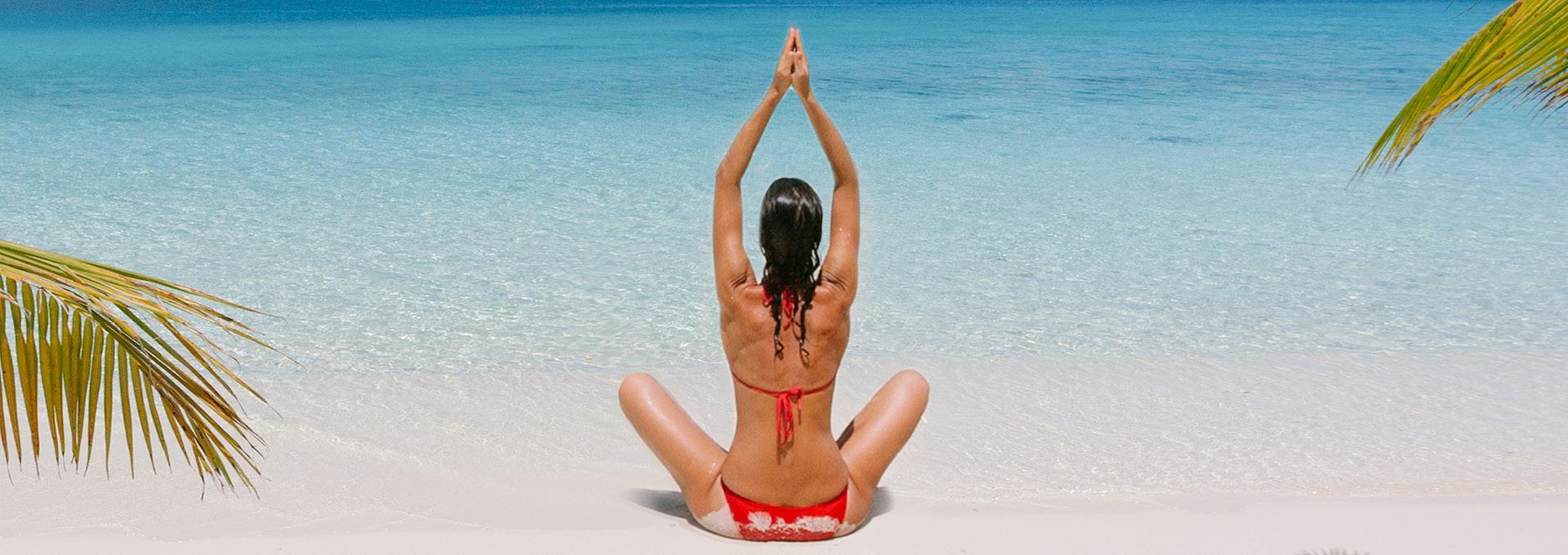 A woman does yoga on the beach