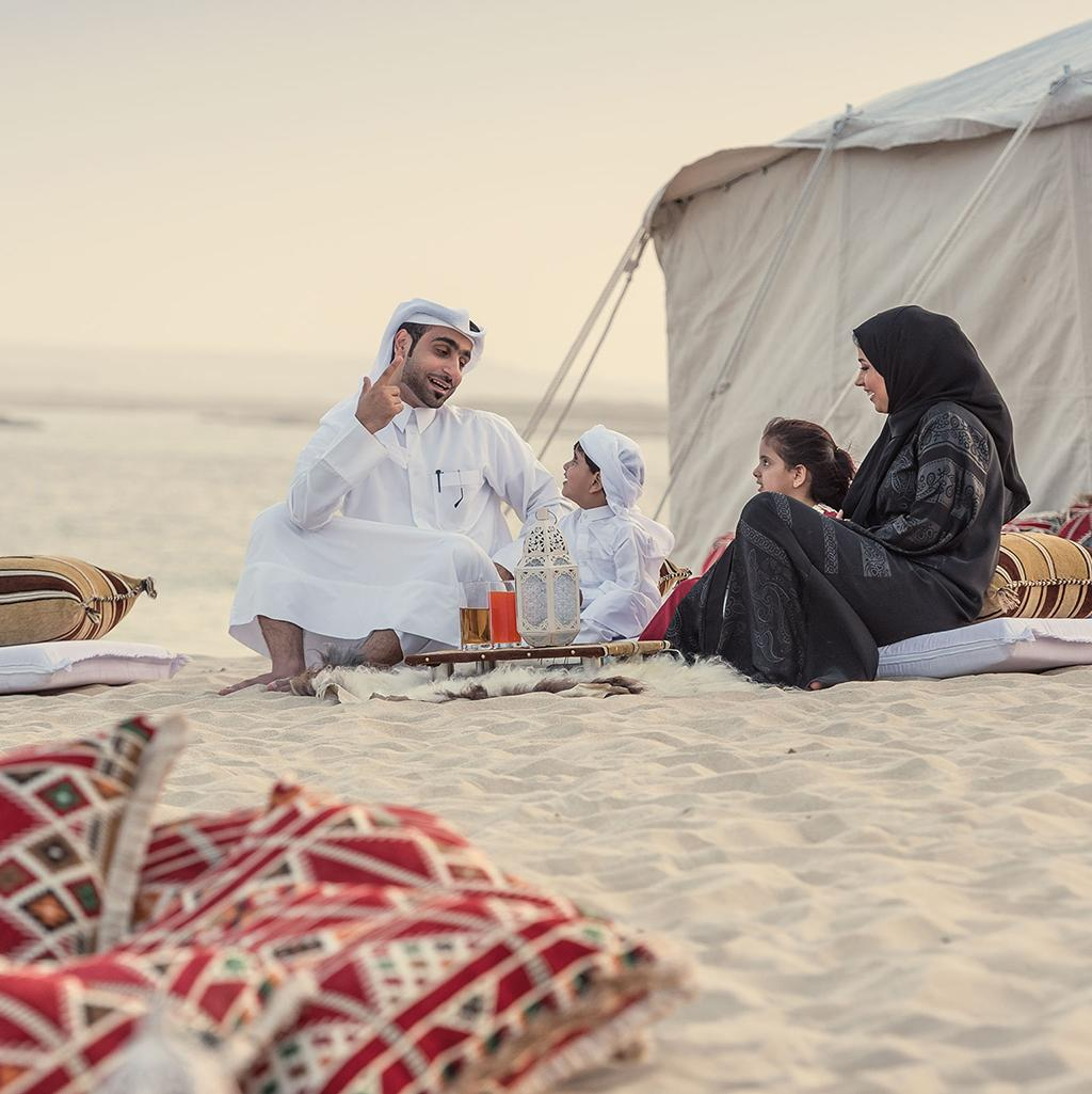 Family in traditional Islamic dress at a Bedouin camp in the desert