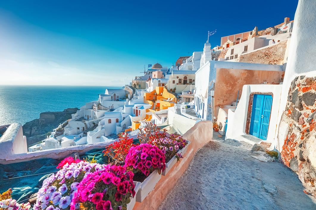 White houses and colorful flowers on the coastline of Santorini
