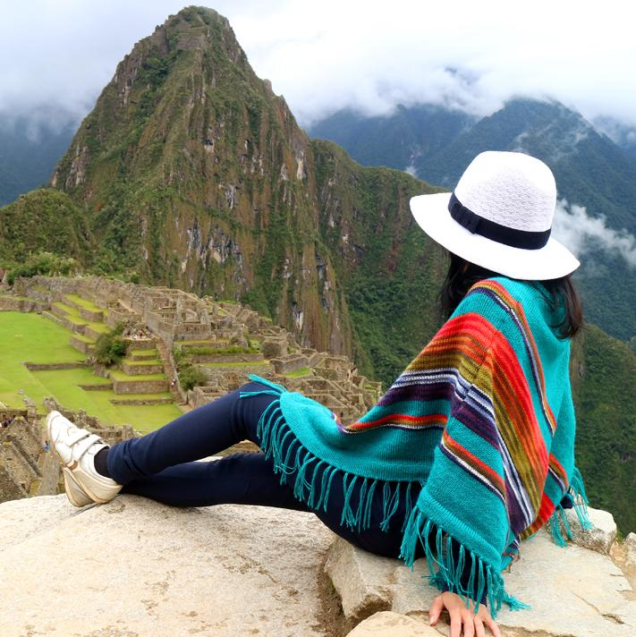 Woman sitting on a rock in a brightly colored poncho overlooking Machu Picchu