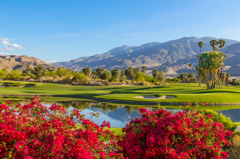 Sunlight washing over a perfectly manicured golf course and mountain range in Palm Springs, California