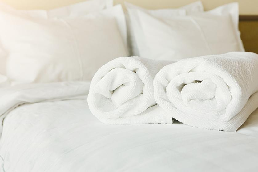 White rolled bath towels and crisp white hotel linens await hotel guests on bed