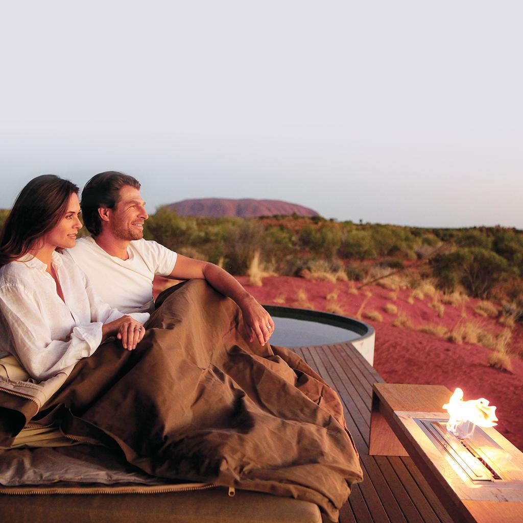 married couple take in the views of Uluru National Park in Australia