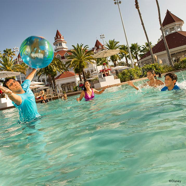 family playing with inflated ball in a resort pool at a Walt Disney World Resort