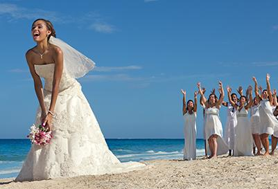 A bride tosses her bouquet on the beach at her destination wedding