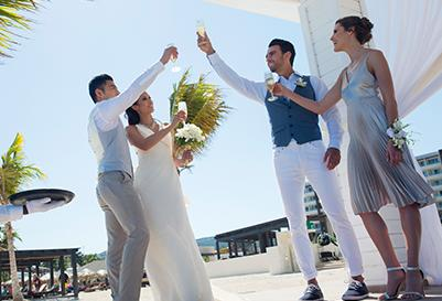 A wedding party toasts on the beach at a destination wedding