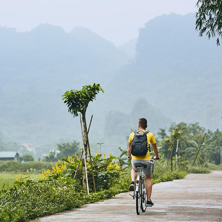 A man bicycles in an exotic location
