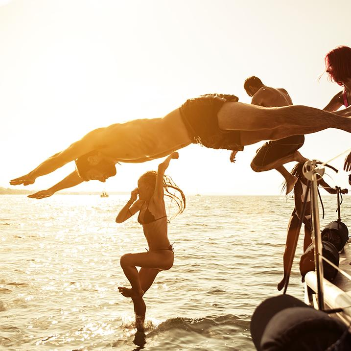 A group of friends jumps into the ocean