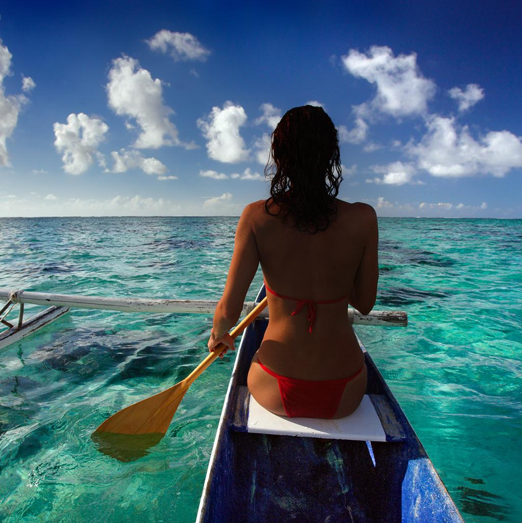 Woman paddling a traditional canoe in Moorea