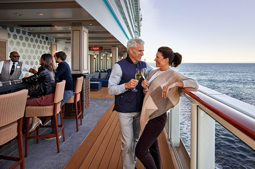couple enjoying drinks and conversation on board the NCL cruise ship bar