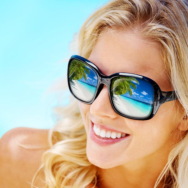 woman in sunglasses with beach views reflecting in the lenses
