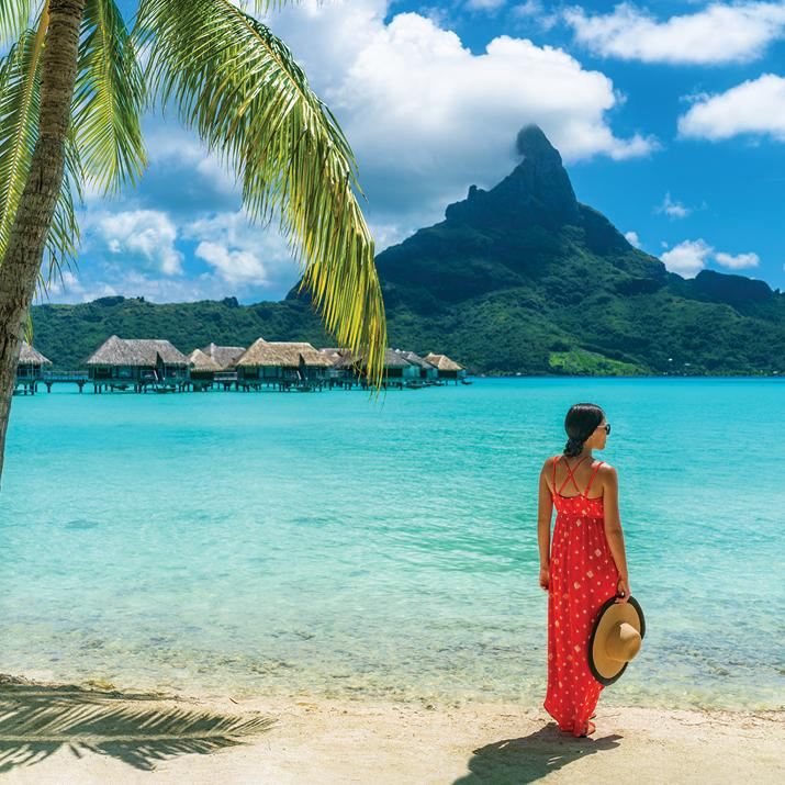 woman in brightly colored sundress on a beach in Tahiti
