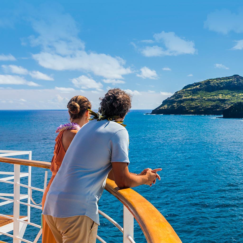 young couple enjoying mountain views on the deck of an NCL cruise ship